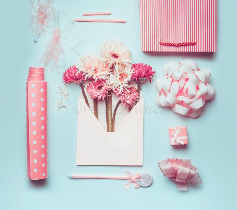 Manojo hermoso fresco de las flores en sobre con los accesorios del saludo: arco, cinta, documento del regalo, pluma y panier sob imagen de archivo libre de regalías