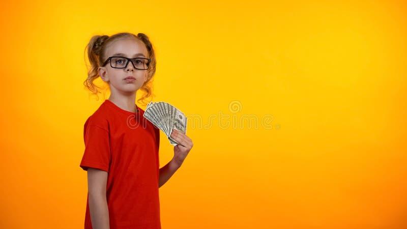 Manojo lindo de efectivo del dólar, concesión que gana del empollón, renta de la tenencia de la muchacha del wunderkind imágenes de archivo libres de regalías