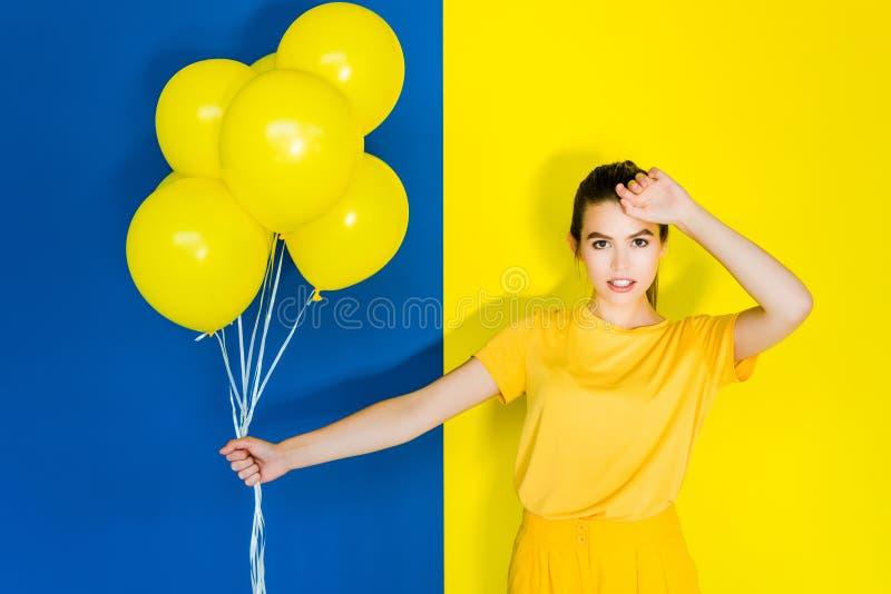 Manojo moreno elegante de la tenencia de la mujer de globos amarillos en azul imagenes de archivo