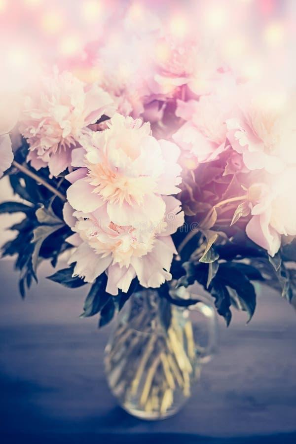 Manojo pálido rosado hermoso de las peonías en el florero de cristal en la tabla con la iluminación del bokeh Ramo romántico de l foto de archivo