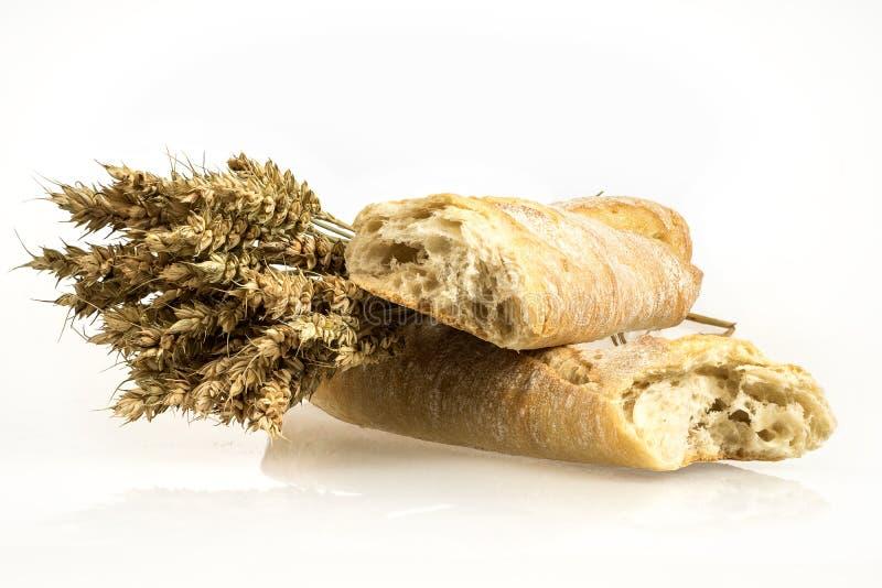 Manojo y baguette del trigo en el fondo blanco Ramo y pan del grano Espiguillas de oro fotos de archivo