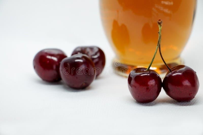 Manojos de cerezas dulces y de una botella de jugo foto de archivo libre de regalías