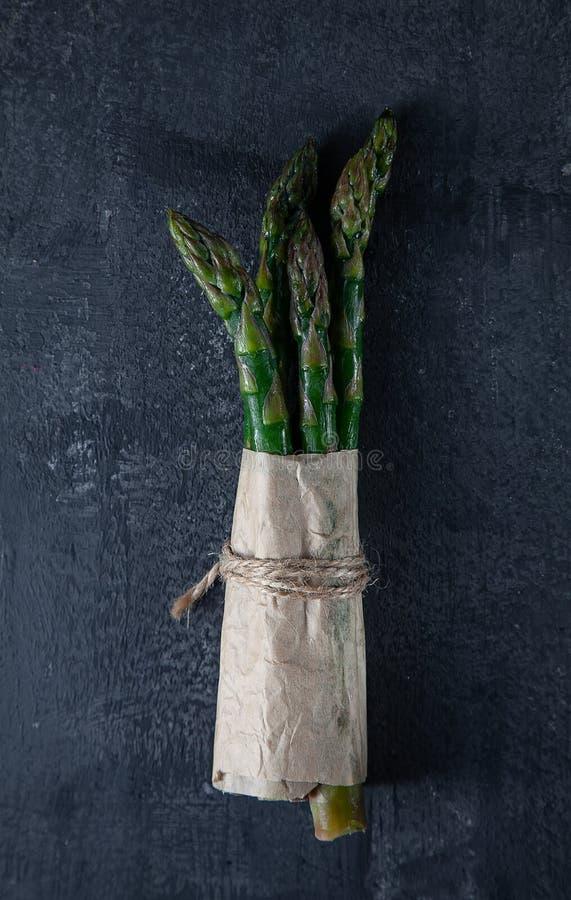 Manojos de espárrago verde fresco en fondo de piedra oscuro Visi?n superior Comida del vegano Ingridients con el espacio de la co imagenes de archivo