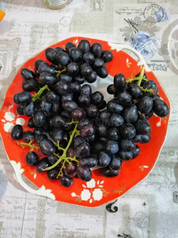 manojos de uvas negras en una placa roja vieja foto de archivo