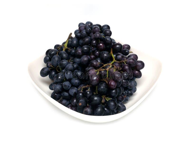 Manojos maduros de la uva en el cuenco blanco aislado foto de archivo