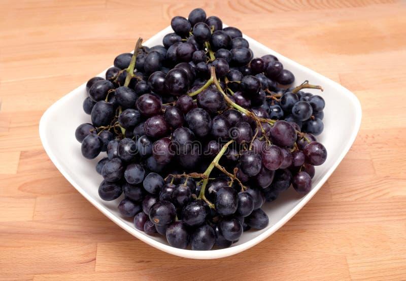 Manojos maduros de la uva en el primer blanco del cuenco fotos de archivo