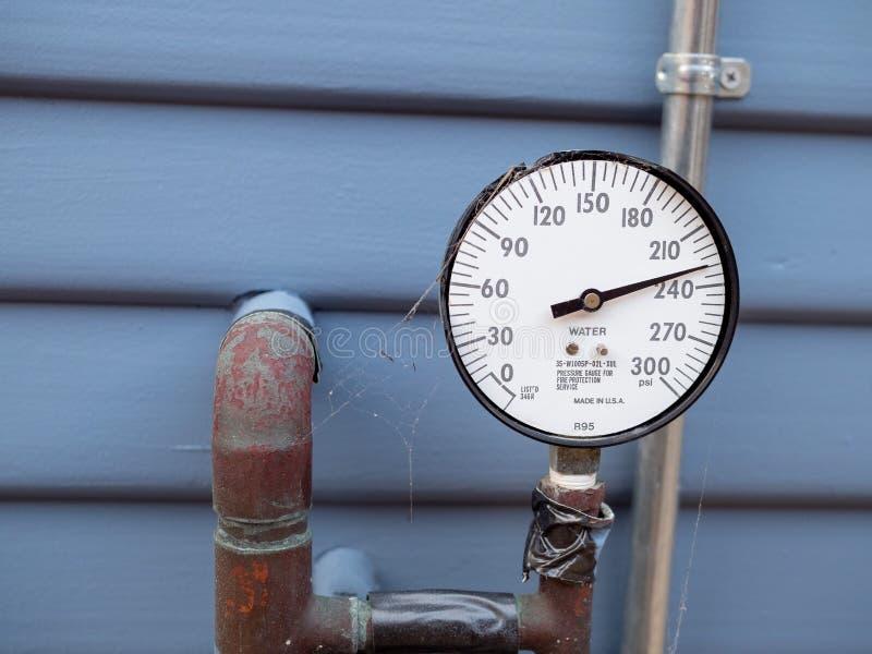 Manomètre d'indicateur de pression de l'eau avec des toiles d'araignée et tuyaux et bande rouillés en dehors de maison Manque de  image stock