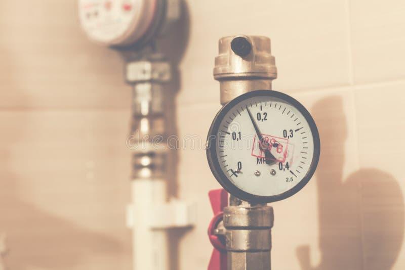 Manomètre de système de tuyauterie central avec le robinet rouge sur la conduite d'eau en plastique du système de tuyauterie image libre de droits