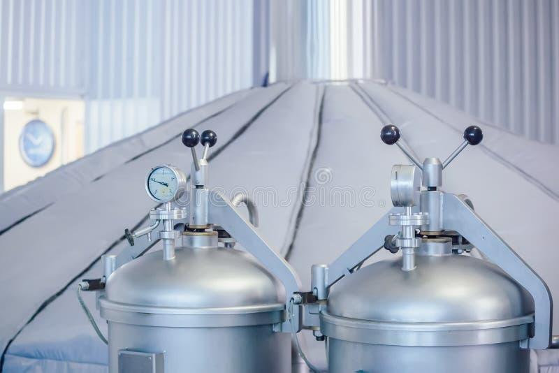Manometer op de cilinder met gas binnen en hopautomaat in moderne brouwerij De mening van de close-up stock afbeelding