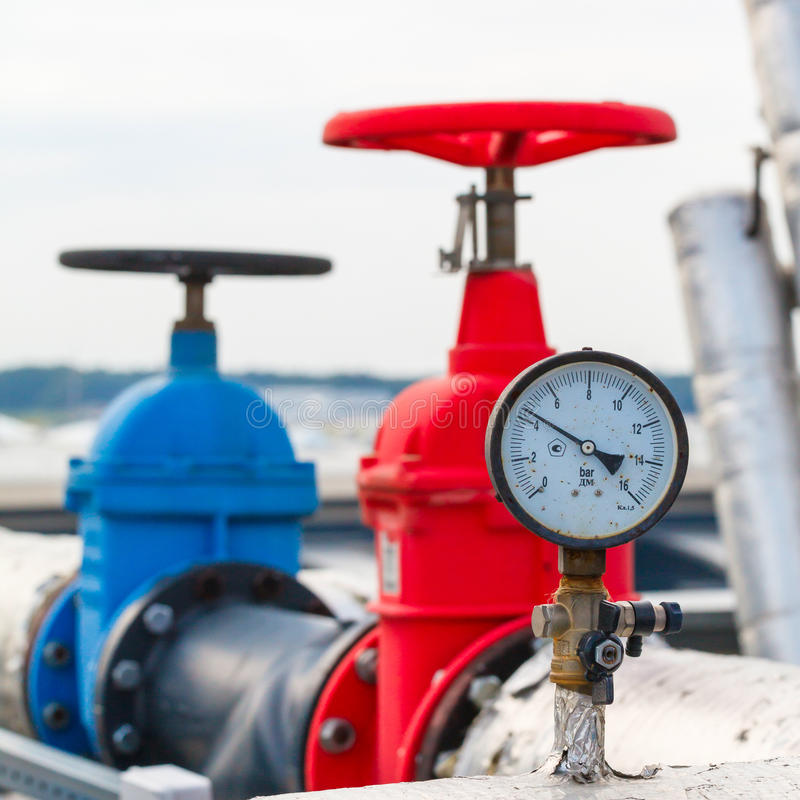 Manometer, red valve on hot pipe. Manometer, red and blue valve on hot and cold pipe royalty free stock images