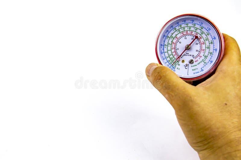 Manometer som mäter trycket av gas för reparationen av kylskåp i handen royaltyfria bilder
