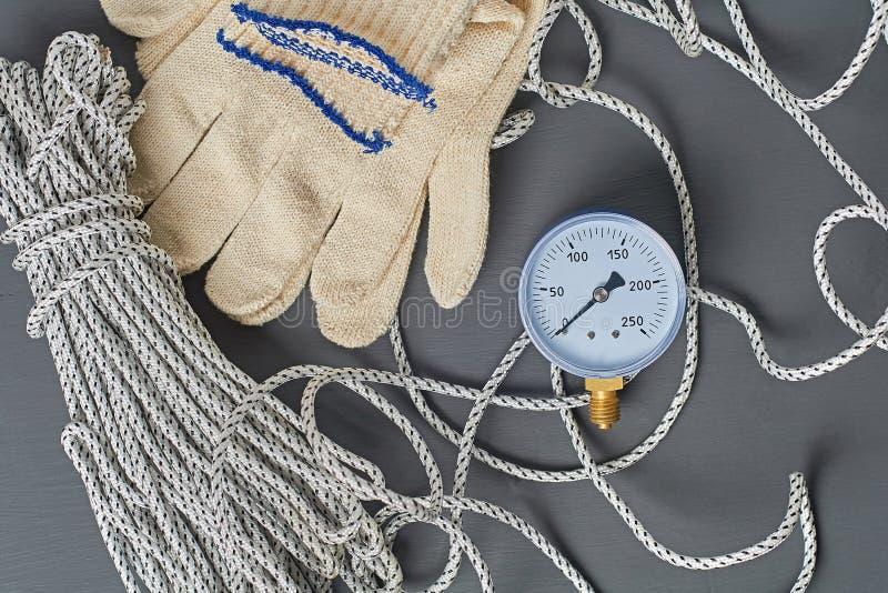 Manometer voor het nauwkeurig meten van de luchtdruk in de buurt van lange sterke touw- en textielhandschoenen stock foto's