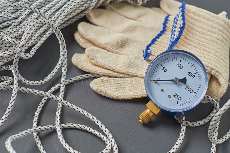 Manometer voor het nauwkeurig meten van de luchtdruk in de buurt van lange sterke touw- en textielhandschoenen stock afbeelding