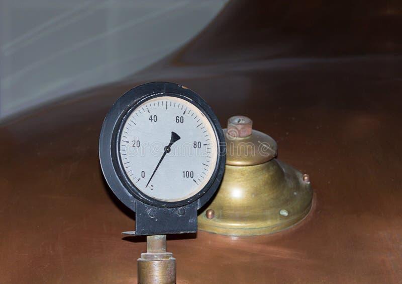 Manometro per determinare la pressione di fronte al carro armato di colore di rame con una valvola della fabbrica della birra immagine stock libera da diritti