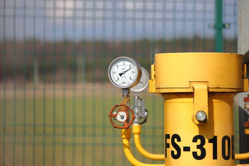 Manometro per la misurazione della pressione di gas naturale in un gasdotto Tubi gialli di trasporto sulla superficie del recinto fotografia stock libera da diritti