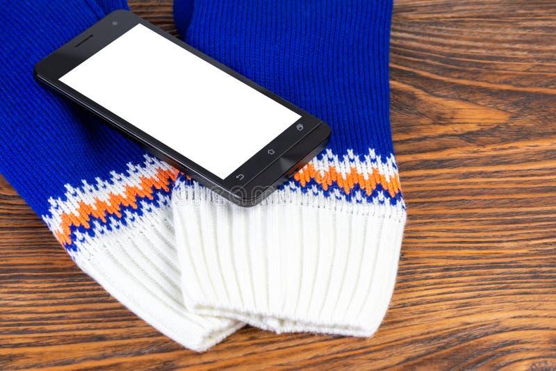 Manoplas knited azules y blancas con el teléfono móvil en fondo de madera imagenes de archivo