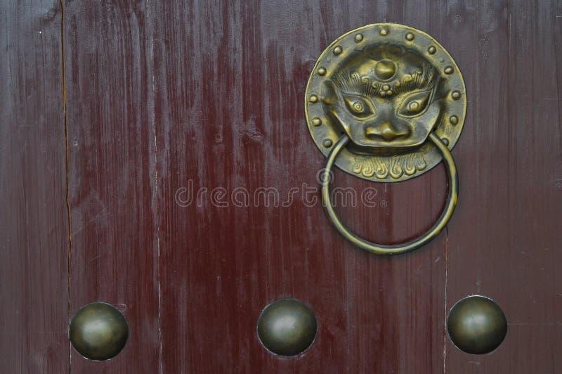 Manopola di porta cinese dell'ornamento del leone dorato d'annata sul portone rosso immagine stock libera da diritti