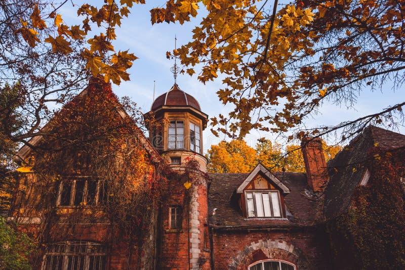 Manor met bomen in de herfstkleuren en dalingsbomen Oud Victoriaans Spookhuis met spoken Verlaten huis in de herfsthout stock afbeeldingen