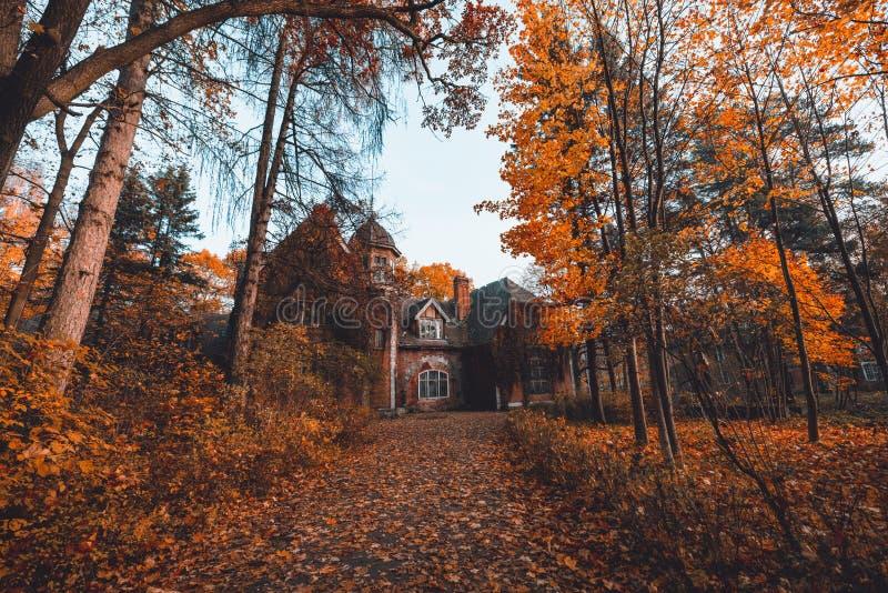 Manor met bomen in de herfstkleuren en dalingsbomen Oud Victoriaans Spookhuis met spoken Verlaten huis in de herfsthout stock foto