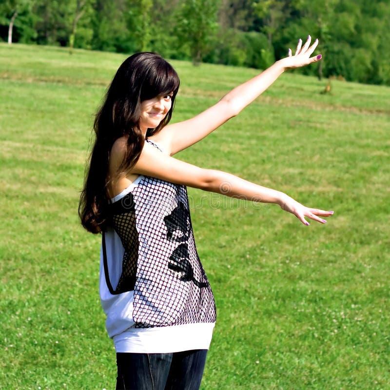 Manos abiertas adolescentes de la sonrisa que se colocan en el prado imagenes de archivo
