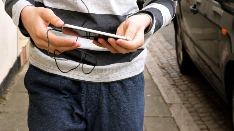 Manos adolescentes con el teléfono elegante que camina y que escucha o que habla en la calle británica adolescente y concepto soc foto de archivo