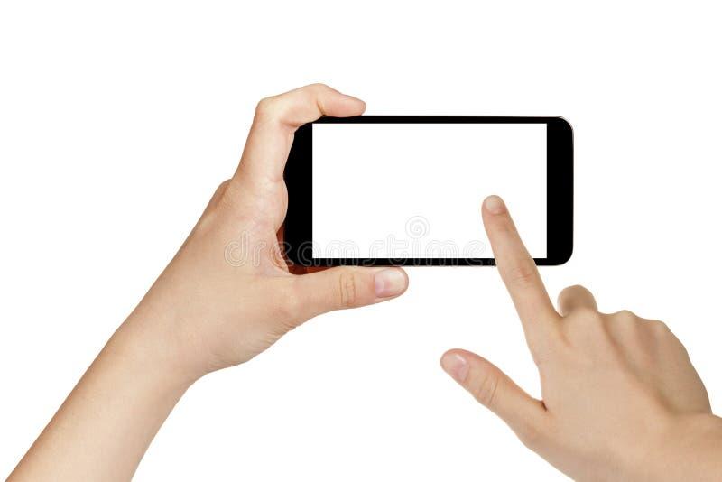 Manos adolescentes femeninas usando el teléfono móvil con la pantalla blanca imagen de archivo