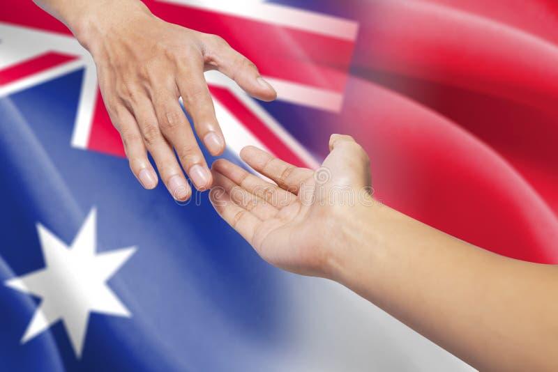 Manos amigas con las banderas australianas e indonesias fotografía de archivo