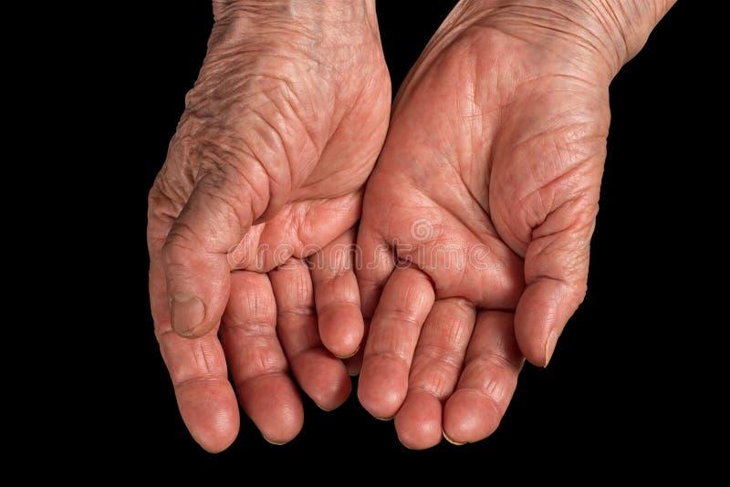 Manos arrugadas mujer mayor Aislado en negro foto de archivo