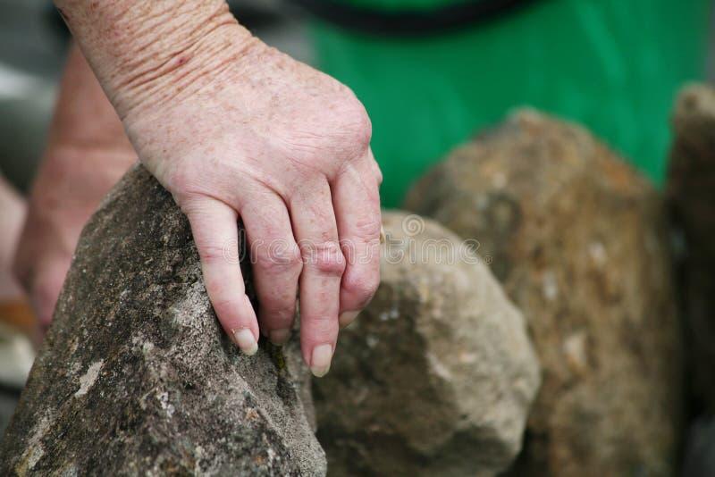 Manos artríticas que mueven rocas imagen de archivo libre de regalías