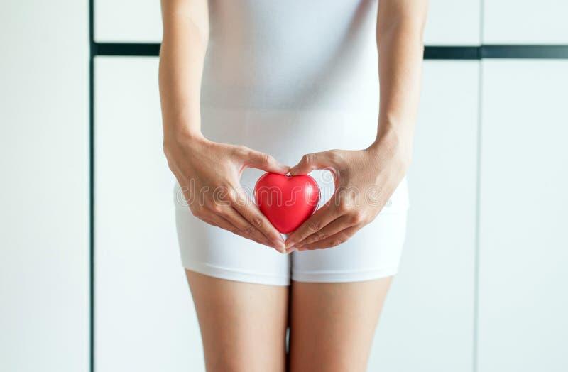 Manos asiáticas de la mujer que llevan a cabo el modelo rojo del corazón en entrepierna con leucorrhoea imágenes de archivo libres de regalías