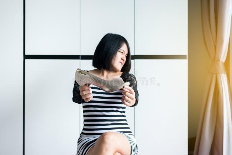 Manos asiáticas de la mujer que sostienen el zapato con el problema del olor y del mún olor, hedor desagradable del pie del rape imagen de archivo libre de regalías