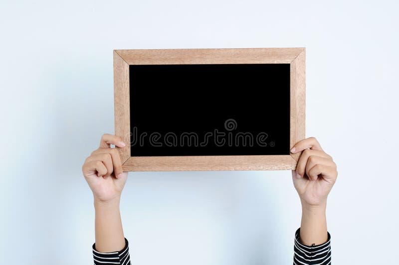 Manos asi?ticas de la mujer que sostienen la pizarra foto de archivo