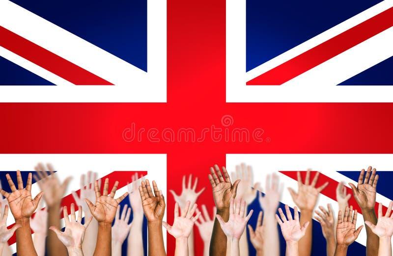 Manos aumentadas con la bandera británica como fondo imágenes de archivo libres de regalías