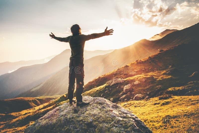 Manos aumentadas hombre feliz en las montañas de la puesta del sol imagen de archivo libre de regalías