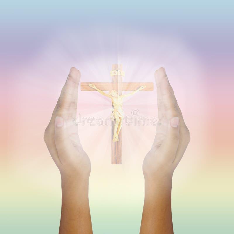 Manos aumentadas rezo para Jesus Christ que brilla intensamente imagen de archivo
