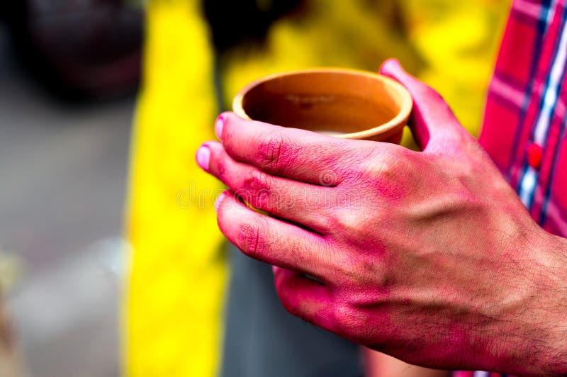 Manos coloridas que sostienen las tazas de la loza de barro de thandai en holi hindú del festival foto de archivo