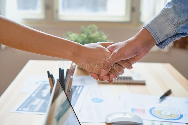 Manos comunes de dos hombres de negocios después de negociar un acuerdo acertado del negocio, y el apretón de manos junto imagen de archivo libre de regalías