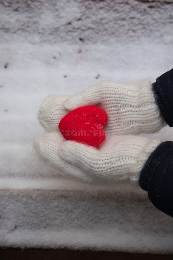 Manos con el corazón rojo en la nieve imagen de archivo libre de regalías