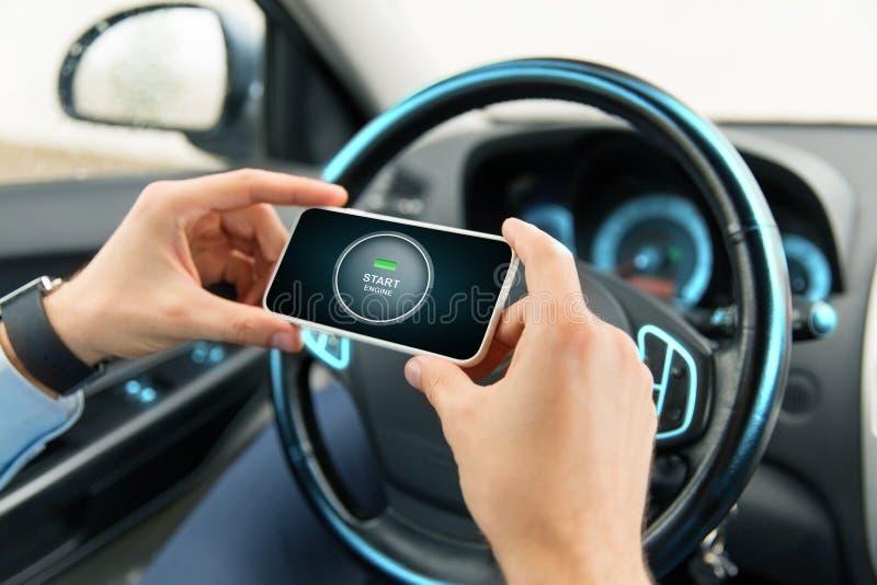 Manos con el icono del motor del comienzo en smartphone en coche imagen de archivo libre de regalías