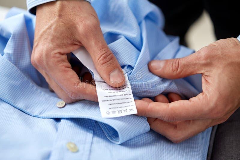 Manos con la camisa y la etiqueta de instrucción de cuidado fotos de archivo