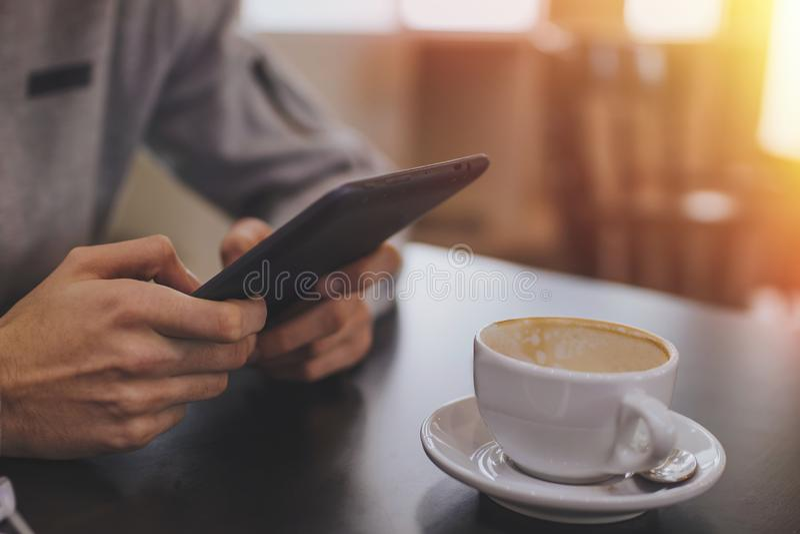 Manos con la tableta o el ebook y el café fotografía de archivo
