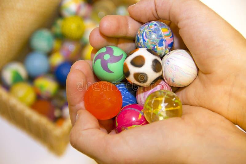 Manos con las bolas coloridas y caja por completo de bolas coloridas foto de archivo libre de regalías