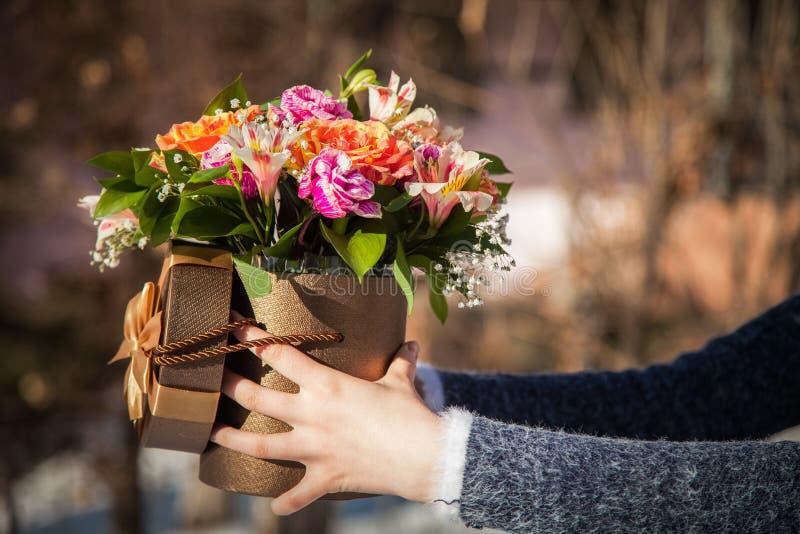 Manos con las flores en la caja foto de archivo libre de regalías