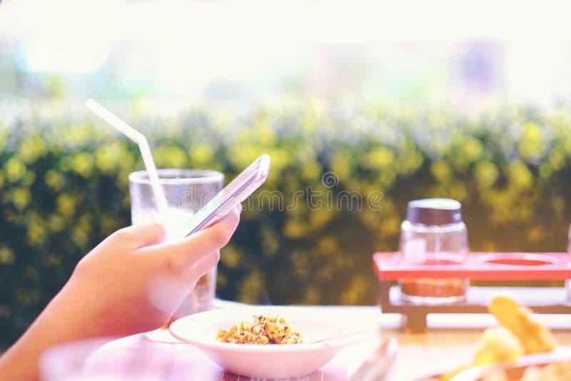 Manos con las imágenes del primer del teléfono del arroz frito de la comida, femal fotografía de archivo libre de regalías