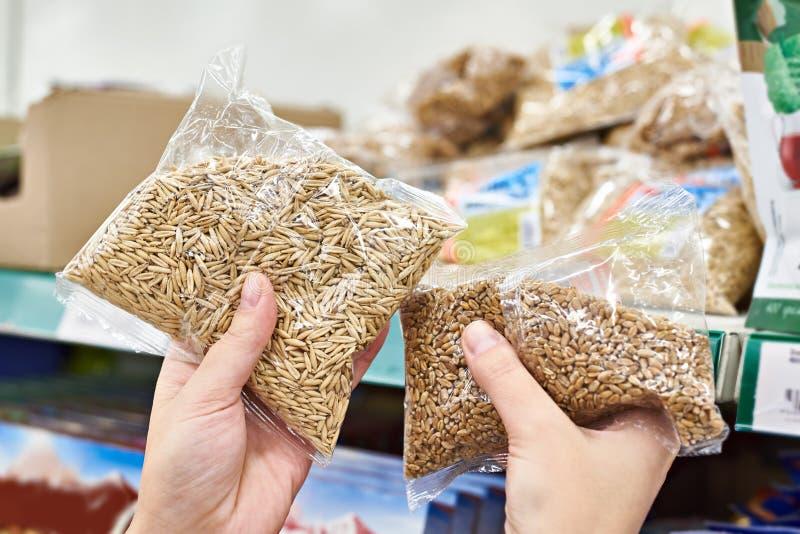 Manos con las semillas de la avena para la comida en tienda imagen de archivo