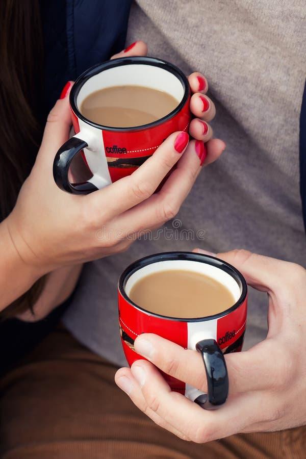 Manos con las tazas de un par de café con leche imagen de archivo libre de regalías