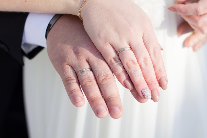 Manos con los anillos de bodas foto de archivo libre de regalías