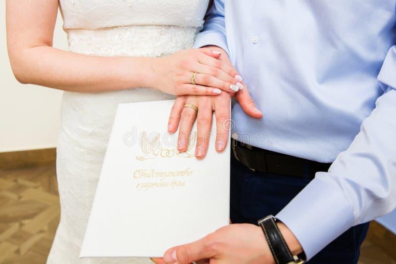 Manos con los anillos de bodas en el certificado del ` de ` de la boda Texto ruso extranjero - certificado de boda imágenes de archivo libres de regalías
