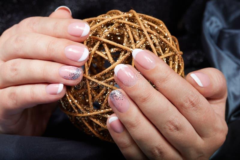 Manos con los clavos manicured franceses que sostienen una bola de oro de la Navidad imagenes de archivo
