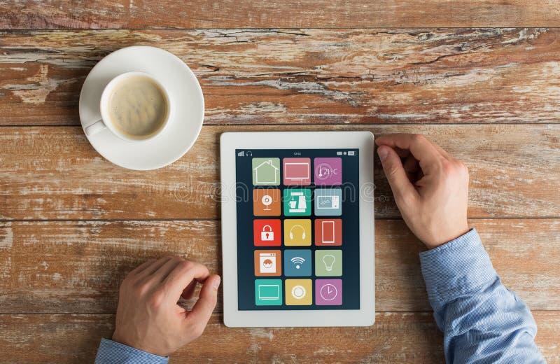 Manos con los iconos caseros elegantes en la tableta imagen de archivo